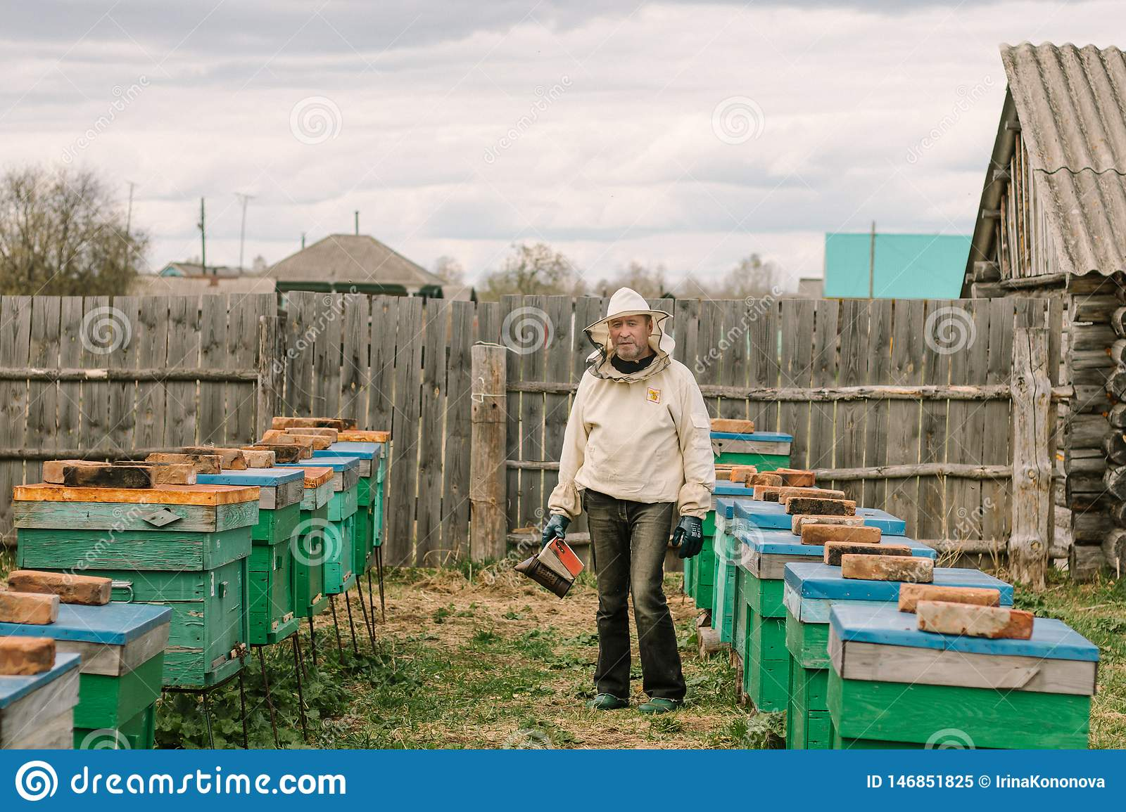 Beekeeper in a protective suit among the hives