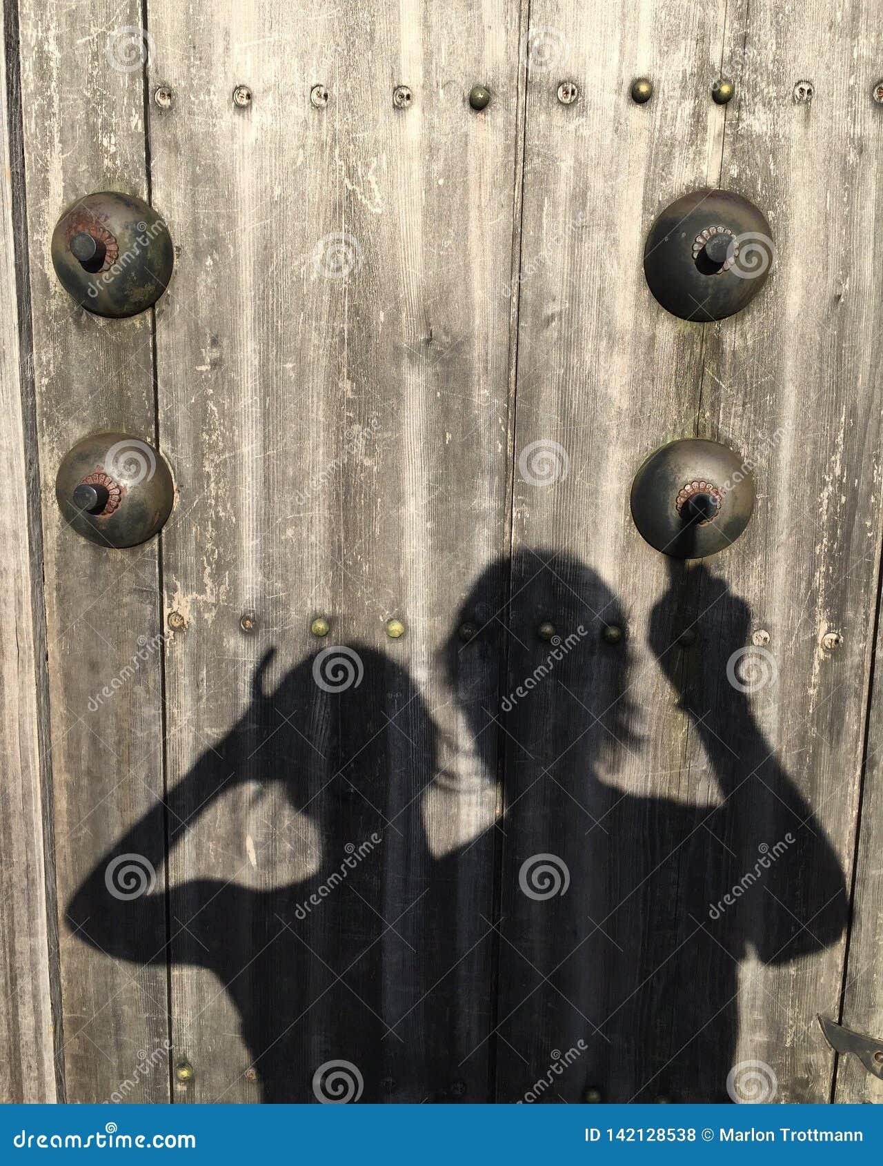 Beeld van de schaduw van vrouwen en een man die op een valse deurbel op een houten deur belt