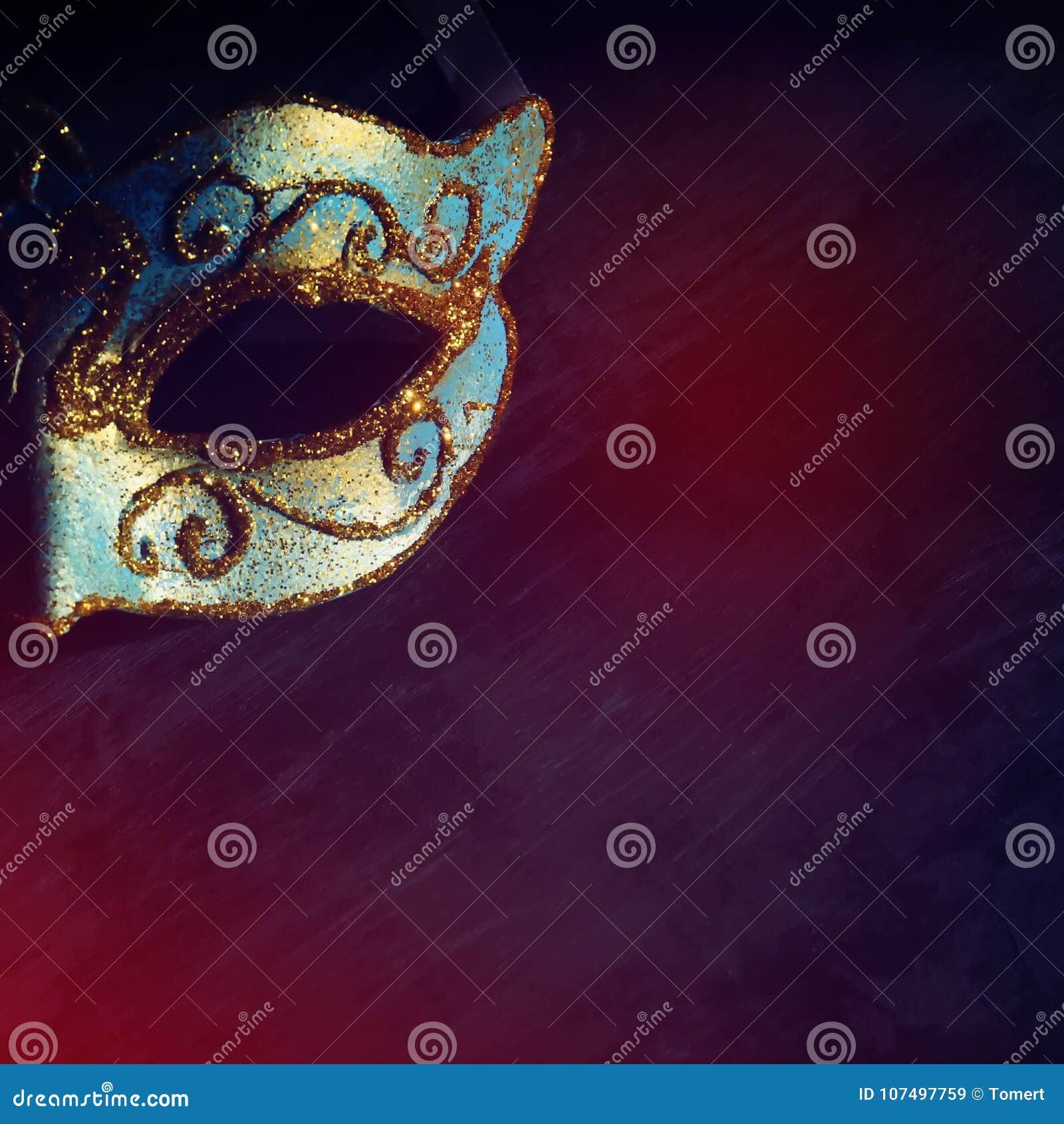 Beeld van elegante blauwe en gouden Venetiaan, het masker van mardigras over zwarte achtergrond