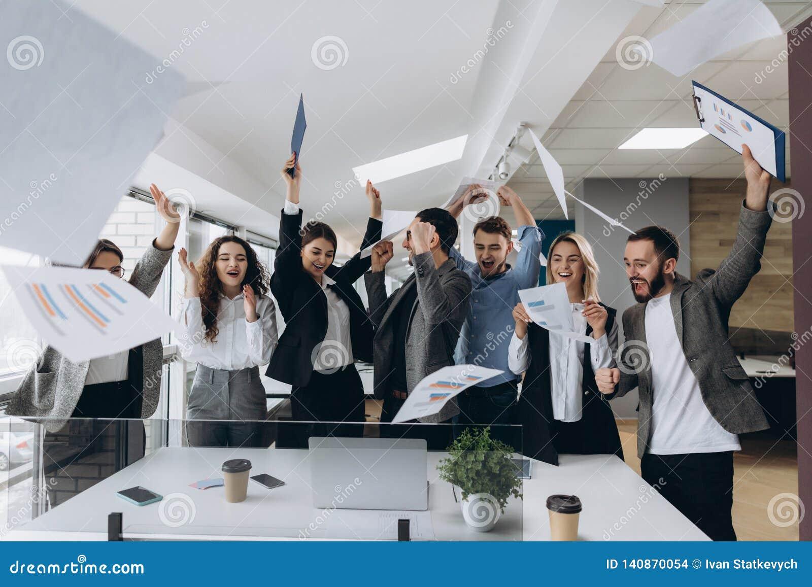Beeld van gelukkige het commerciële team vieren overwinning in bureau Het succesvolle commerciële team werpt stukken van document