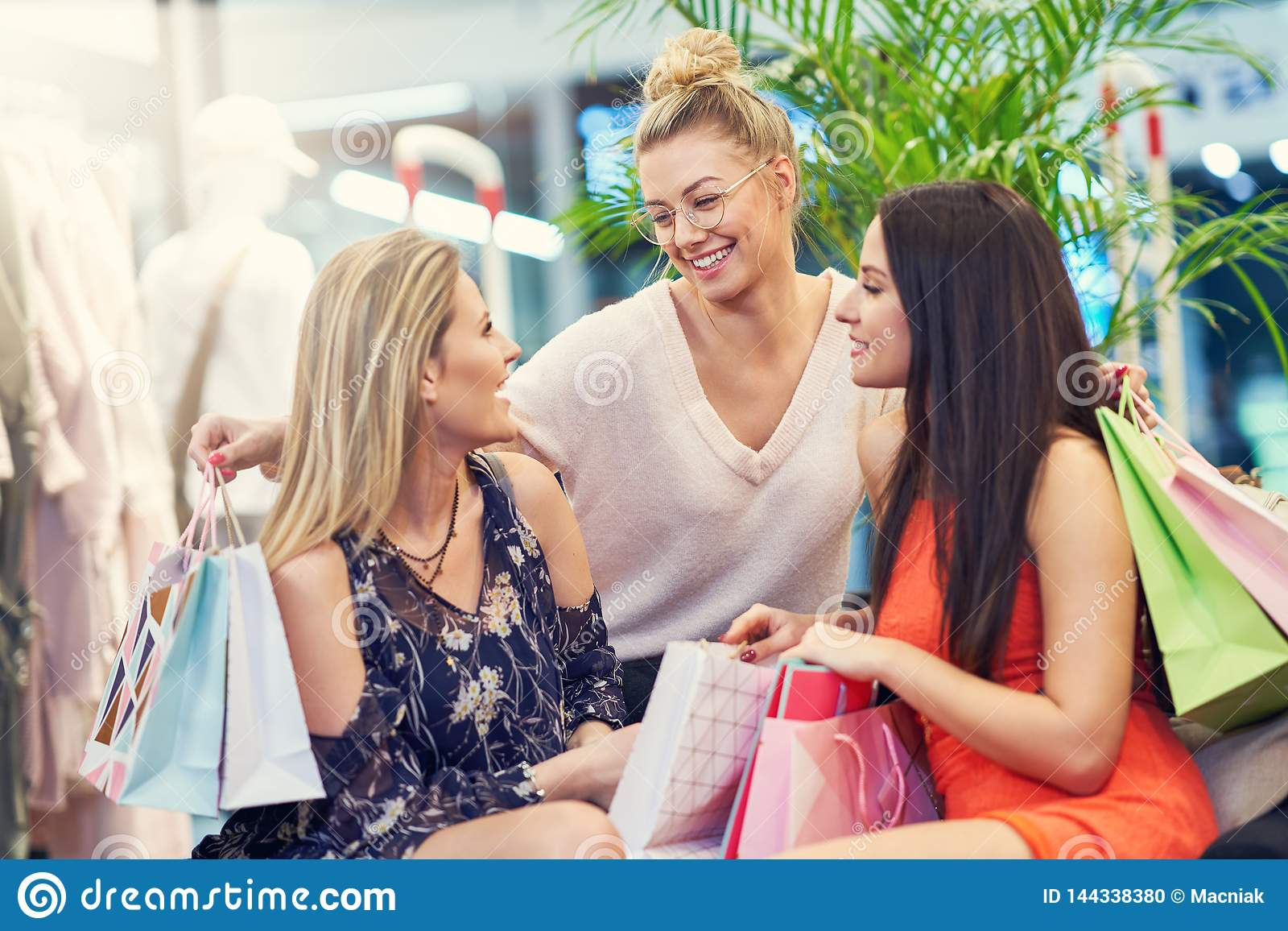 Beeld van groep gelukkige vrienden die voor kleren in wandelgalerij winkelen