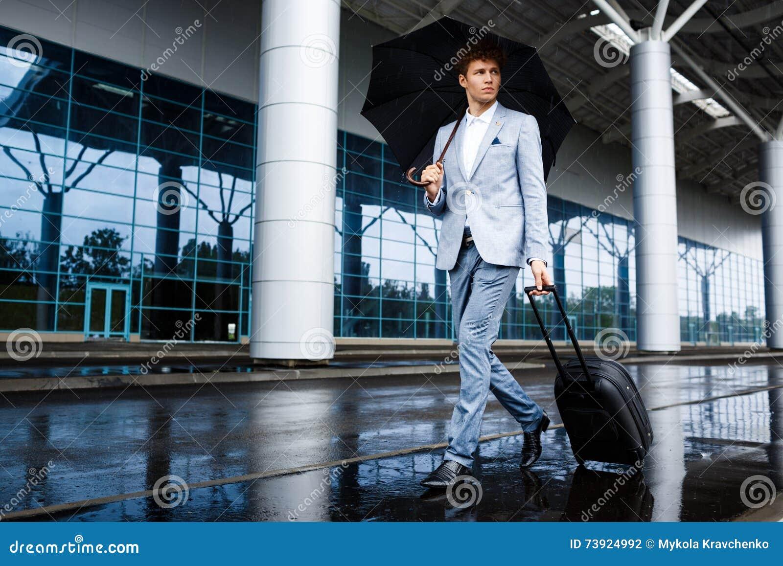 Beeld van jonge redhaired zakenman zwarte paraplu houden en koffer die in regen bij luchthaven lopen