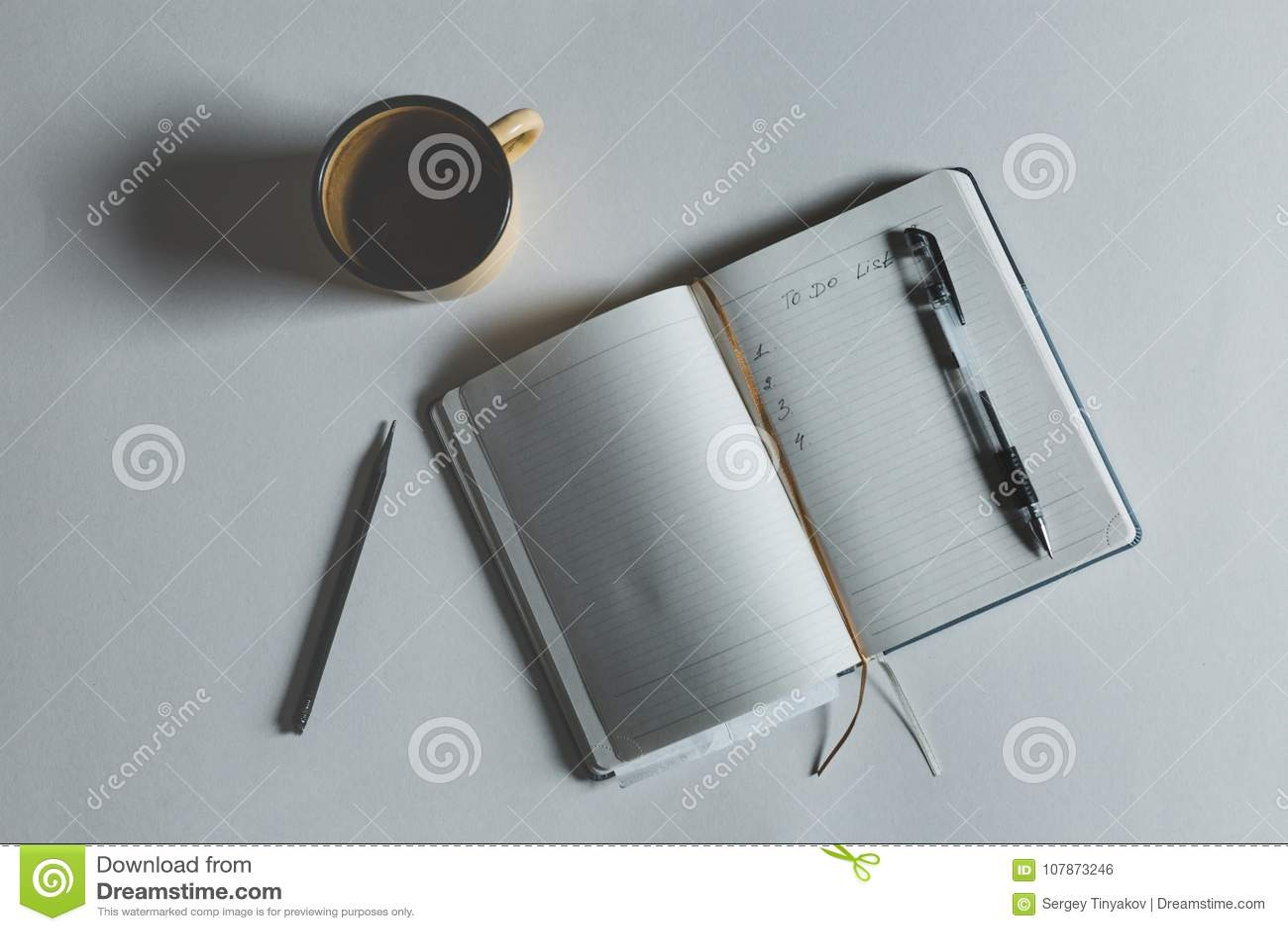 Beeld van Open Notitieboekje met Tekst om Lijst naast Kop van Koffie op hoogste mening te doen