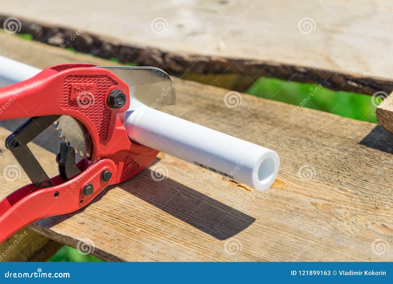 Beeld van scherpe plastic pijp door speciale rode schaar
