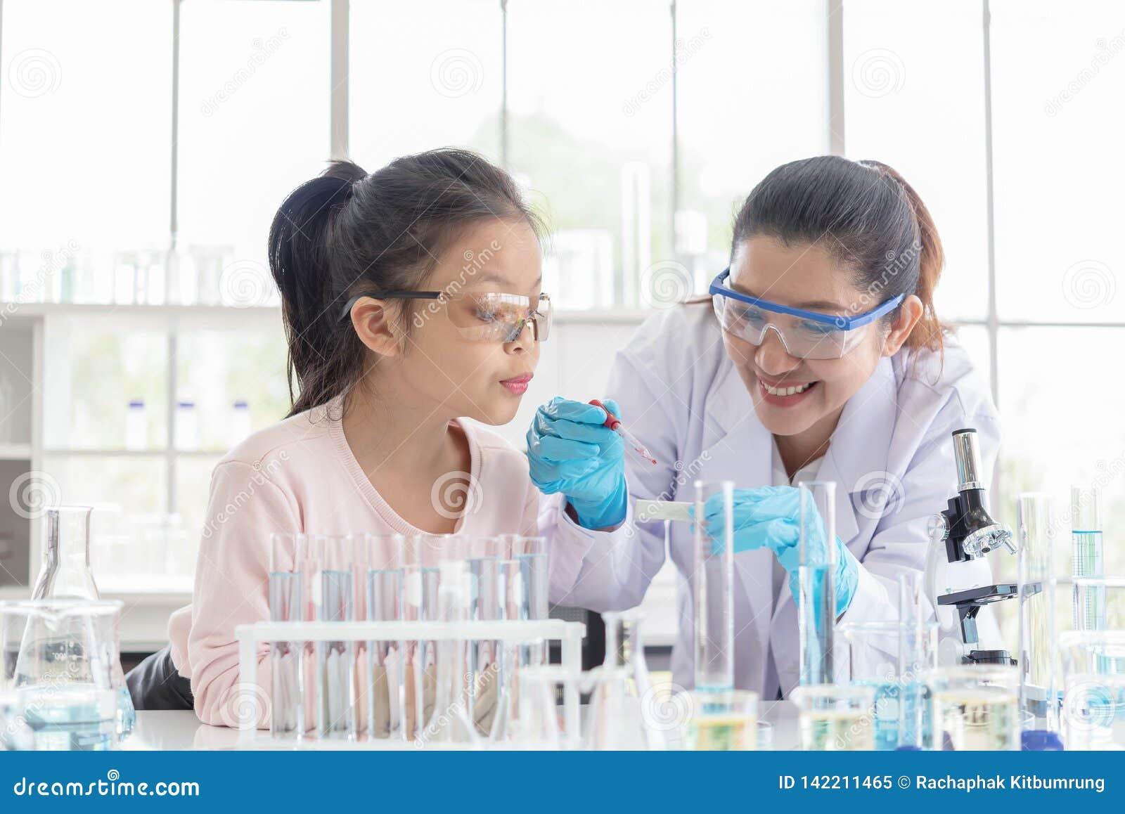 Beeld van vrouwenleraar en studente in de klasse van de laboratoriumwetenschap Jong die meisje in laboratoriumklasse wordt opgewe