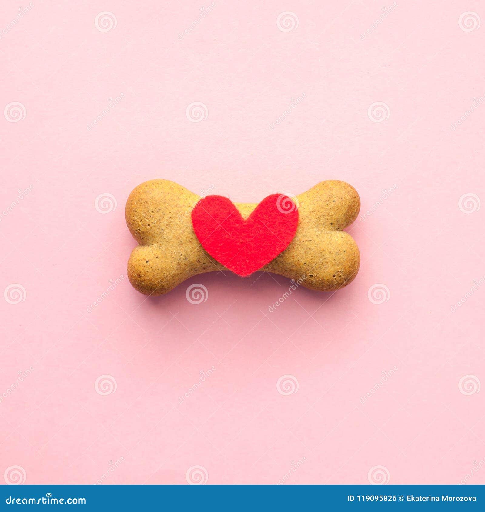Been-vormig koekje voor hond en rood hart op roze achtergrond, de zorg van het conceptenhuisdier