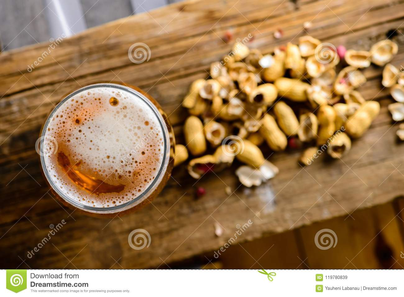 Beer glass with dark cold beer with bubble froth and peanuts on