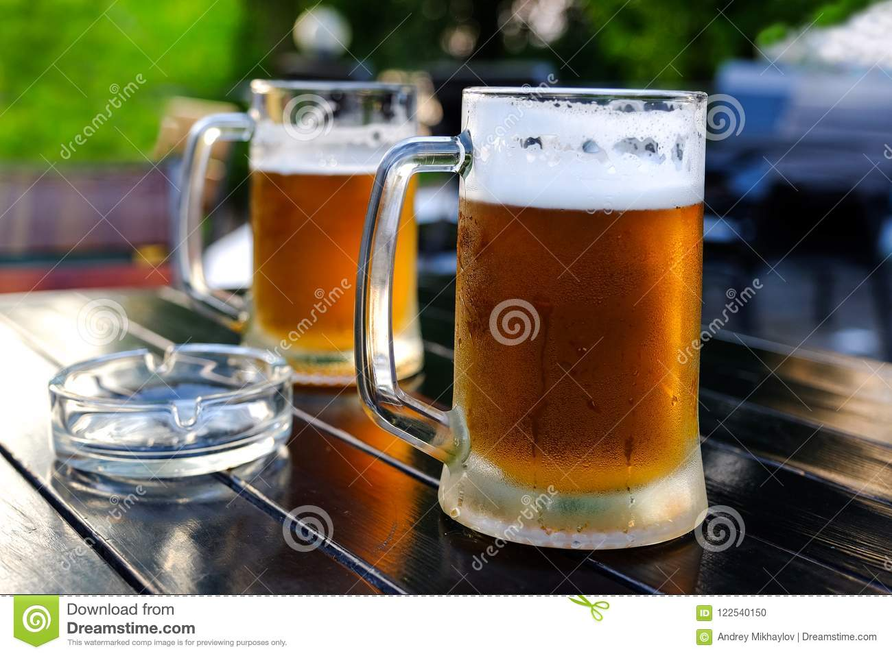 Beer in a glass glass glass, bubbles rise. On the background of green foliage glass with Golden drops.