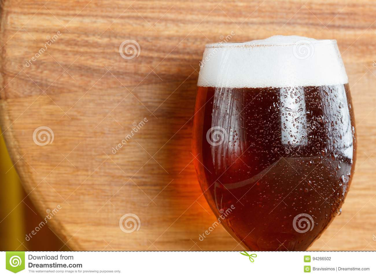 Beer glass pint with copy-space on wooden background.