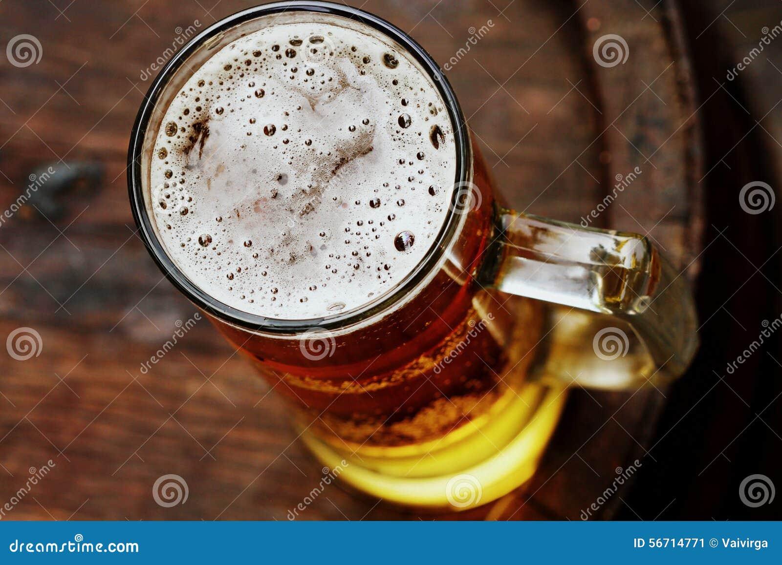 Beer glass on wooden barrel
