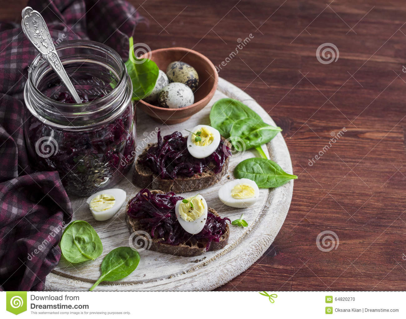 Beetroot relish and a sandwich with beets, quail egg and spinach on rustic light wooden board.