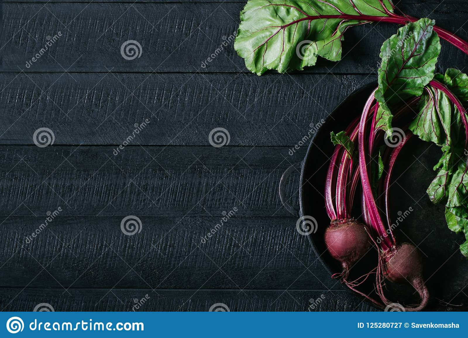 Beets with green tops in round metal pan on dark black wooden background, fresh red beetroot on backdrop kitchen table top view