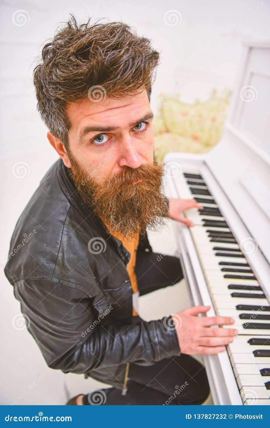 Begaafd musicusconcept De mens in leerjasje zit dichtbij piano muzikaal instrument in wit binnenland op achtergrond Mens