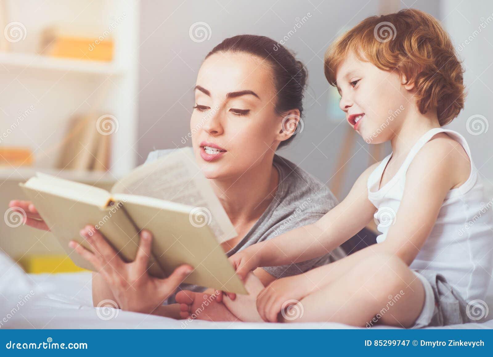 Begeisterte Mutter, die Märchen zu ihrem Sohn liest
