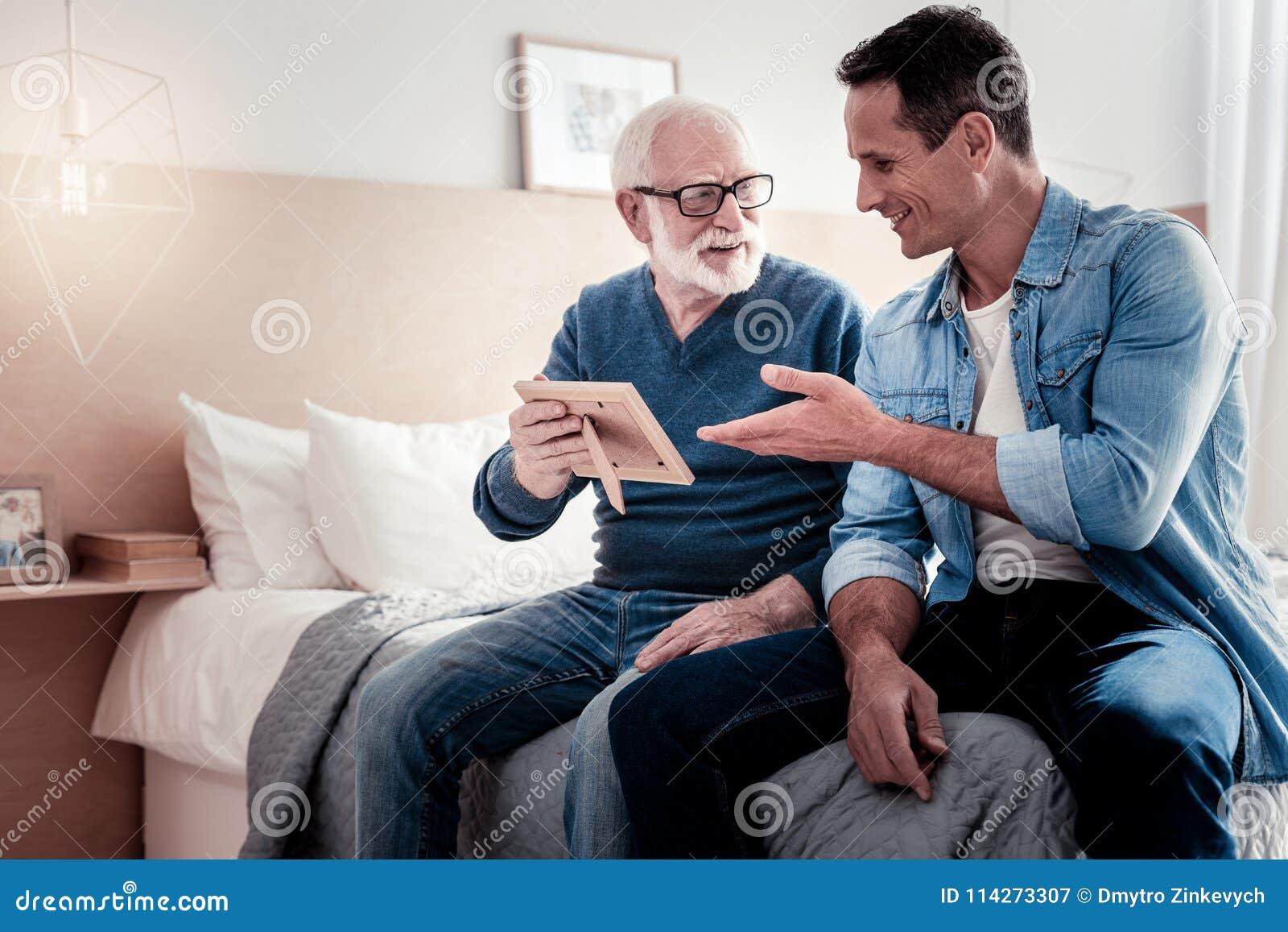 Begeisterter gealterter Mann, der ein Foto hält