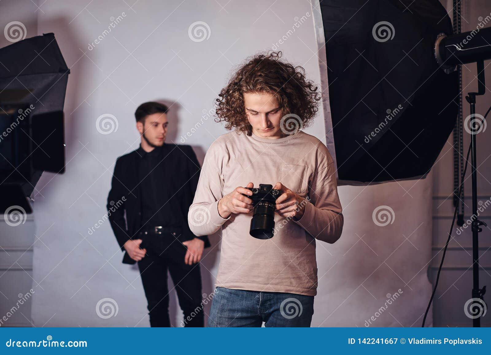 Beginnerfotograaf bij een fotospruit in een studio met een elegant geklede kerel