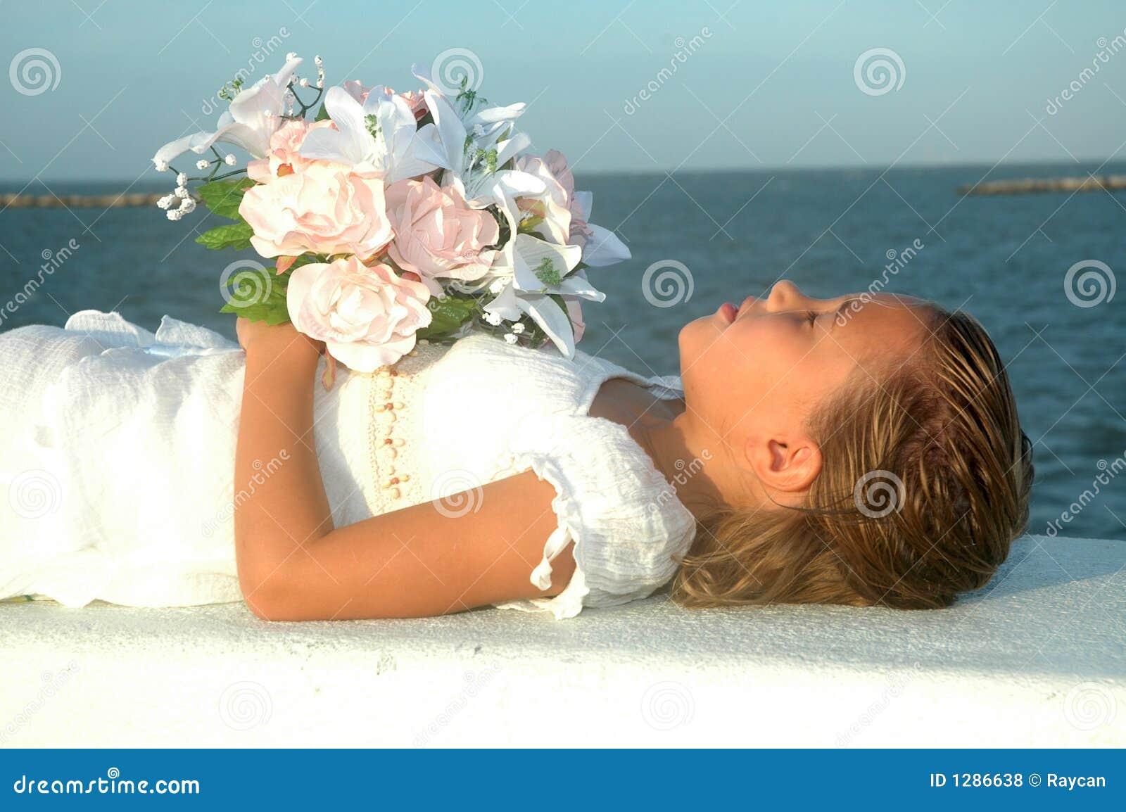 Het jonge kind beweert in slaap naast de oceaan te zijn. Zij imiteert ...