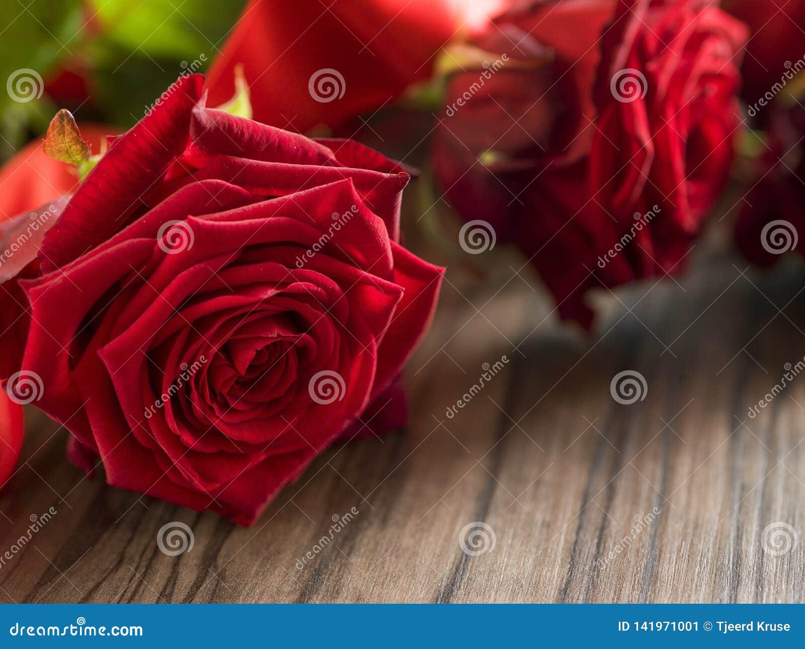 Begrafenis en het rouwen rood concept - nam bloem op houten doodskist toe