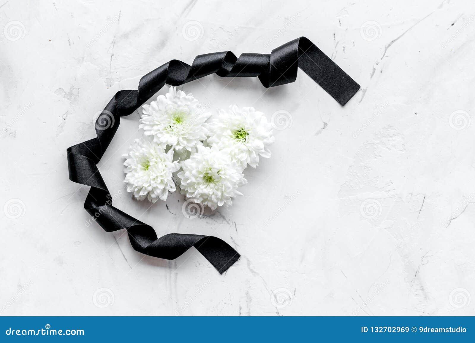 Begravnings- symboler Vit blomma nära svart band på utrymme för kopia för bästa sikt för vitstenbakgrund