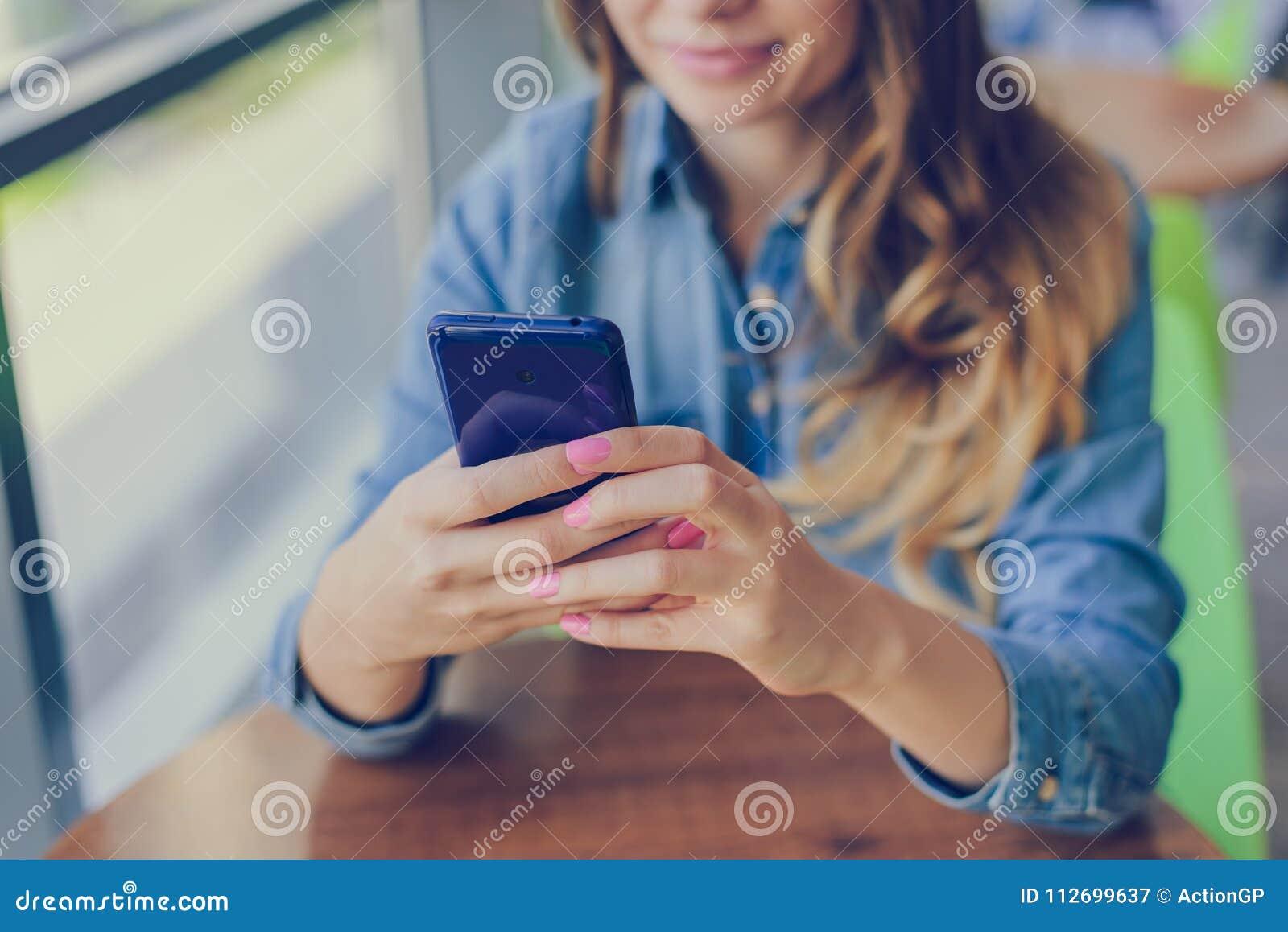 Begrepp av att använda modern teknologi för att shoppa Den lyckliga le kvinnan använder mobiltelefonen för internetshopping, henn