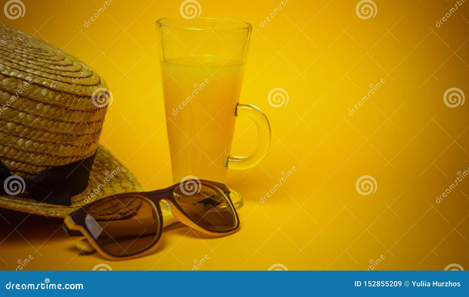 Begrepp av avkoppling och som törstar på stranden ett exponeringsglas av lemonad på en gul bakgrund med solglasögon och en sugrör