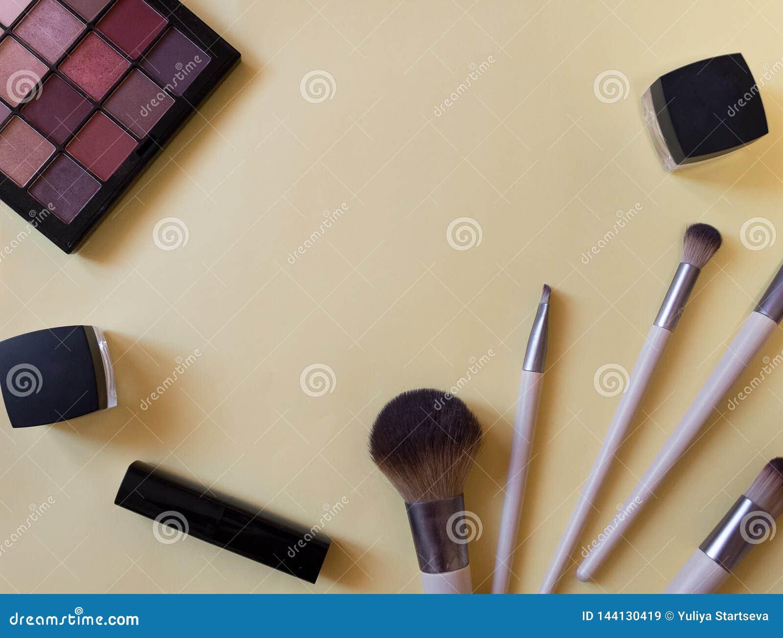 Begrepp av bästa sikt för kosmetiska rör och för kräm- behållare på rosa bakgrund Läppstift borste, palett