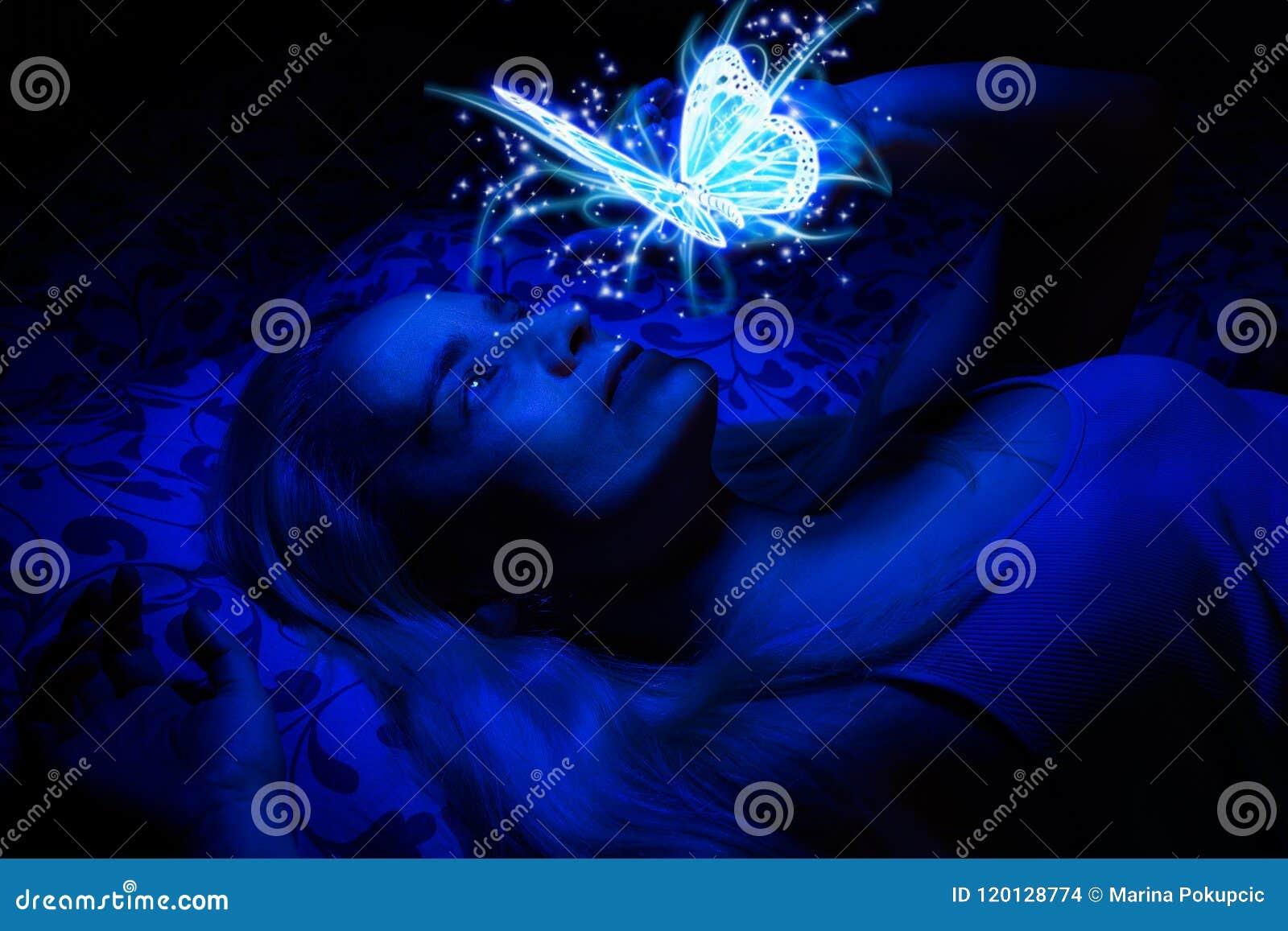 Begrepp av en kvinna som lägger i säng i mörkret som är upplyst med blått ljus från att sväva den magiska fjärilen
