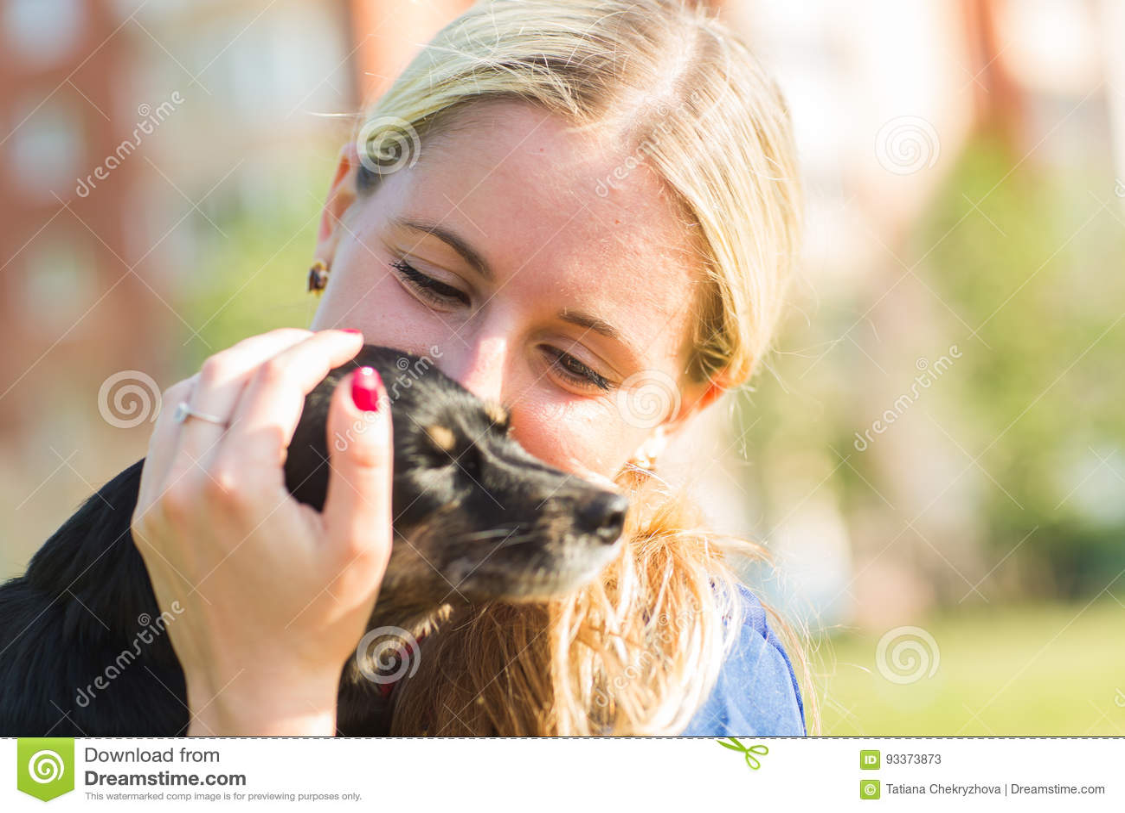 Begrepp av husdjur och den lyckliga ägaren - kvinnan rymmer en hund utomhus