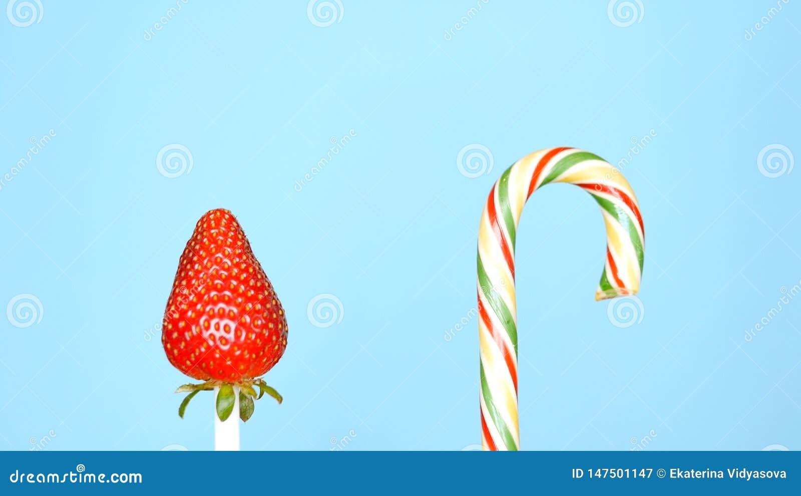 Begrepp av sund och sjuklig mat jordgubbe mot godisen p? en ljus bl? bakgrund