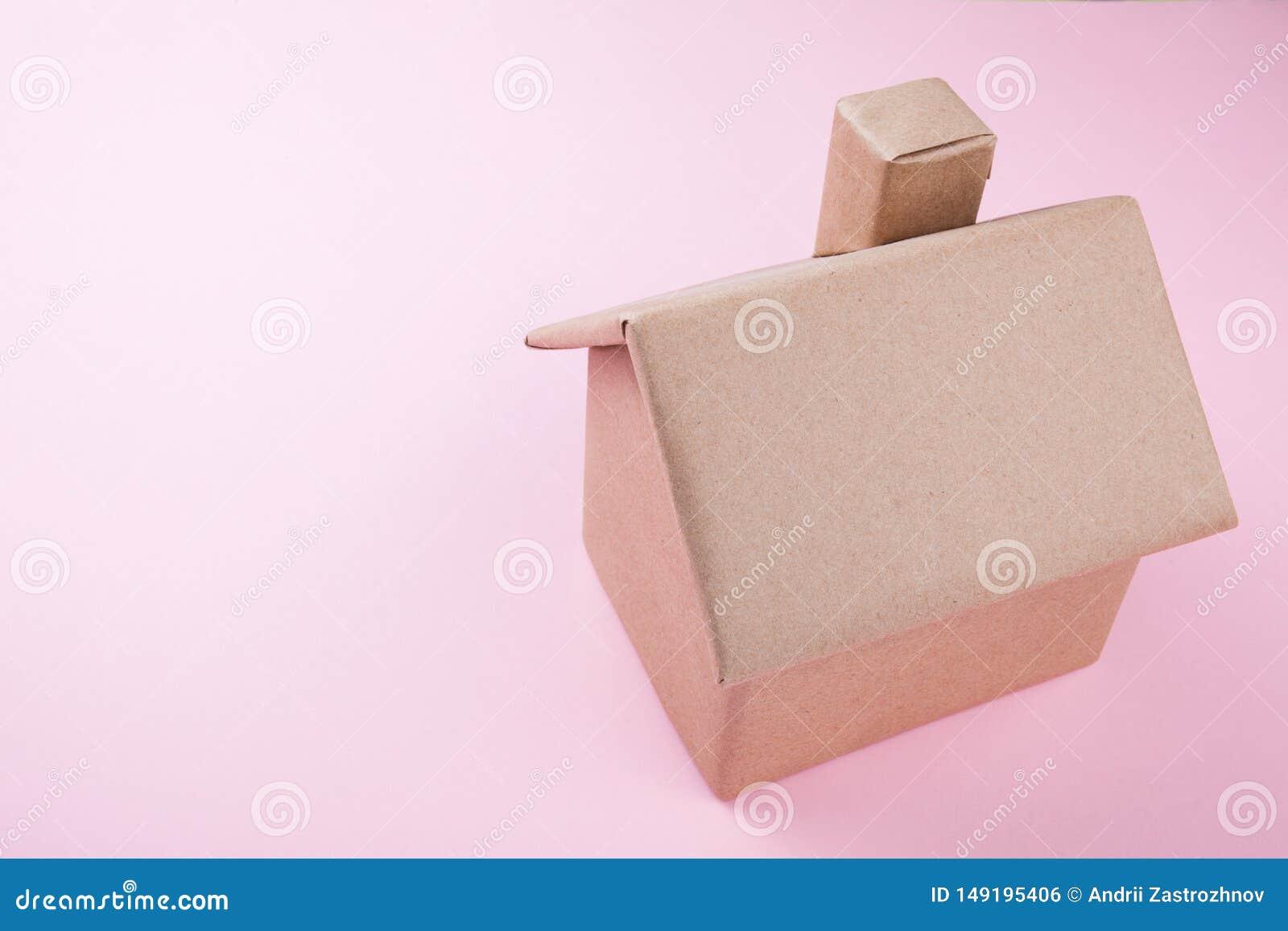 Begrepp ett hus som göras av wellpapp, isolerat på en rosa bakgrund placera text