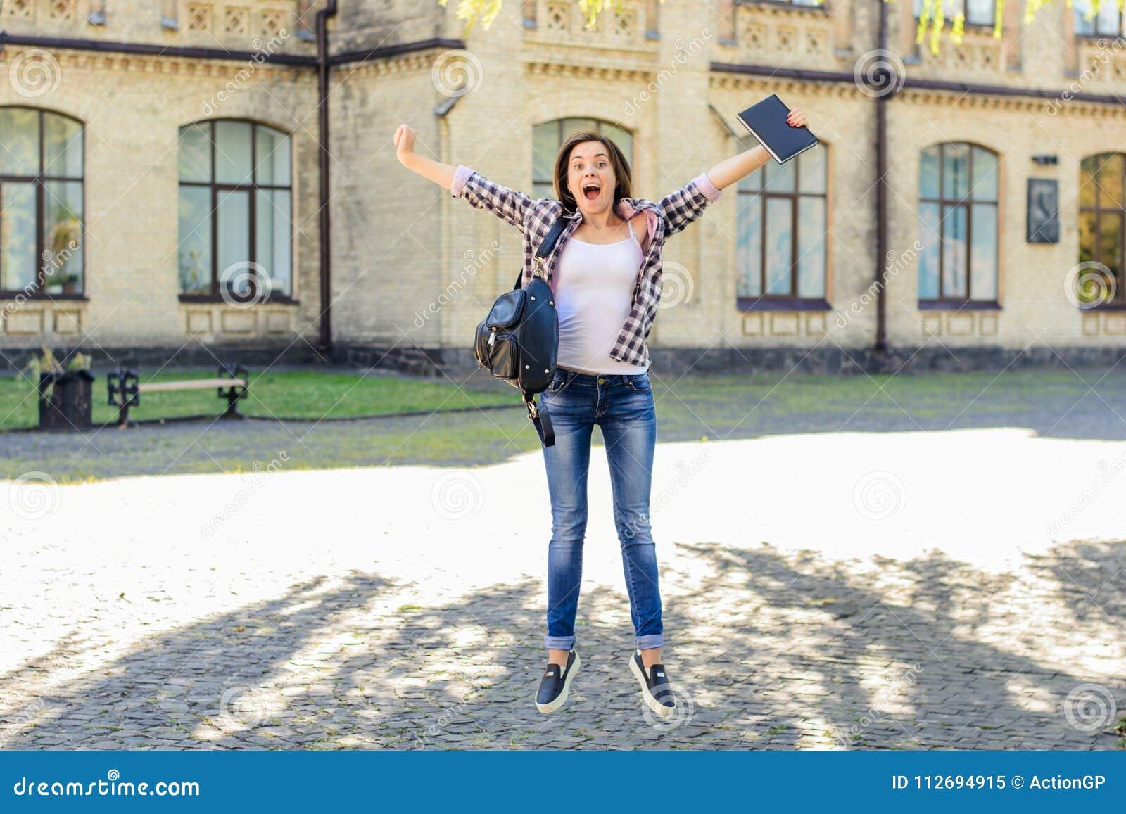 Begrepp för byggnad för högskola för utbildning för luch för examenprestation bra Kvinnlig student för lycklig upphetsad banhoppn