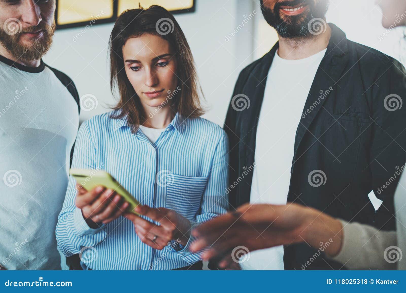 Begrepp för Coworkersaffärsmöte Unga kvinnor som rymmer den mobila smartphonehanden och diskussionsnyheterna med hennes kollegor