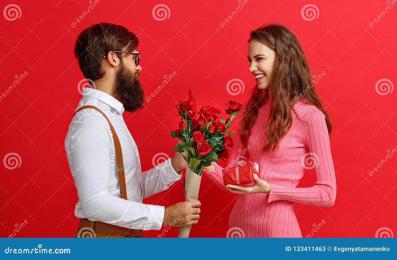 Begrepp för dag för valentin` s lyckliga unga par med hjärta, blommor