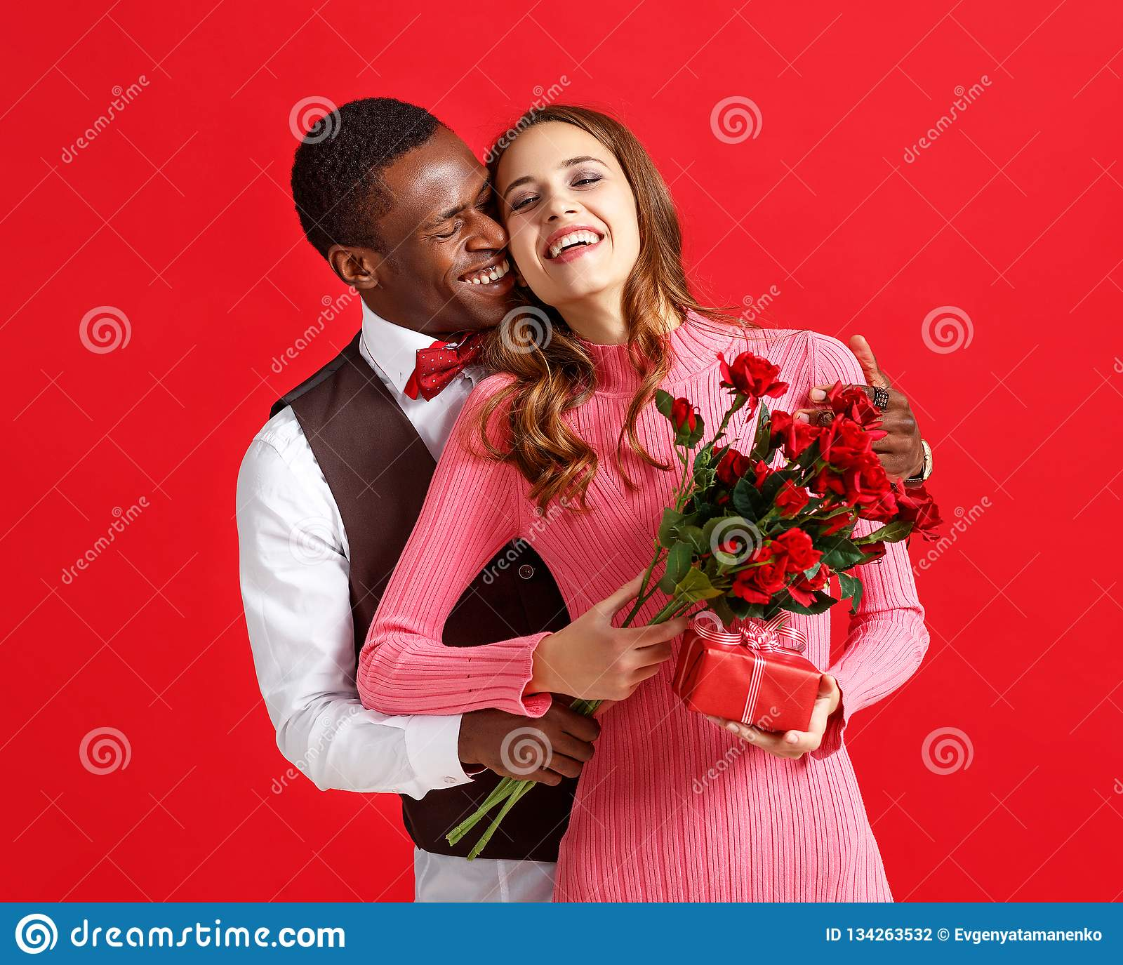 Begrepp för dag för valentin` s lyckliga unga par med hjärta, blommor, gåva på rött