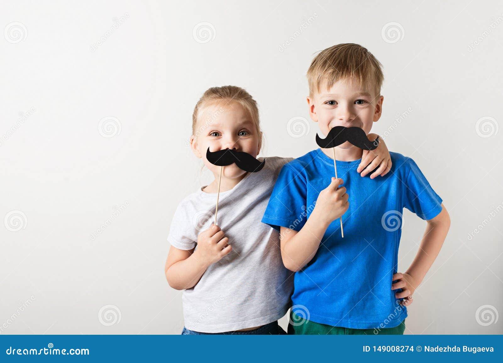 Begrepp f?r faderdag, tv? lilla caucasian ungar som ler med mustaschen p? vit bakgrund
