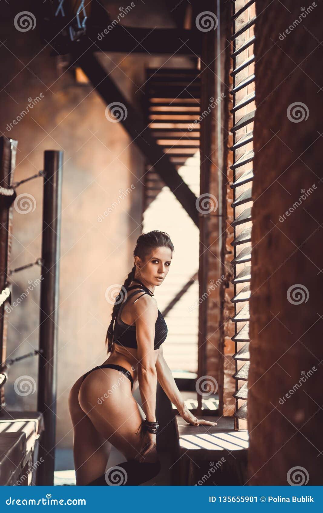 Begrepp för genomkörare för konditionstyrkautbildning - sexig sportflicka för muskulös kroppsbyggare som gör övningar i idrottsha