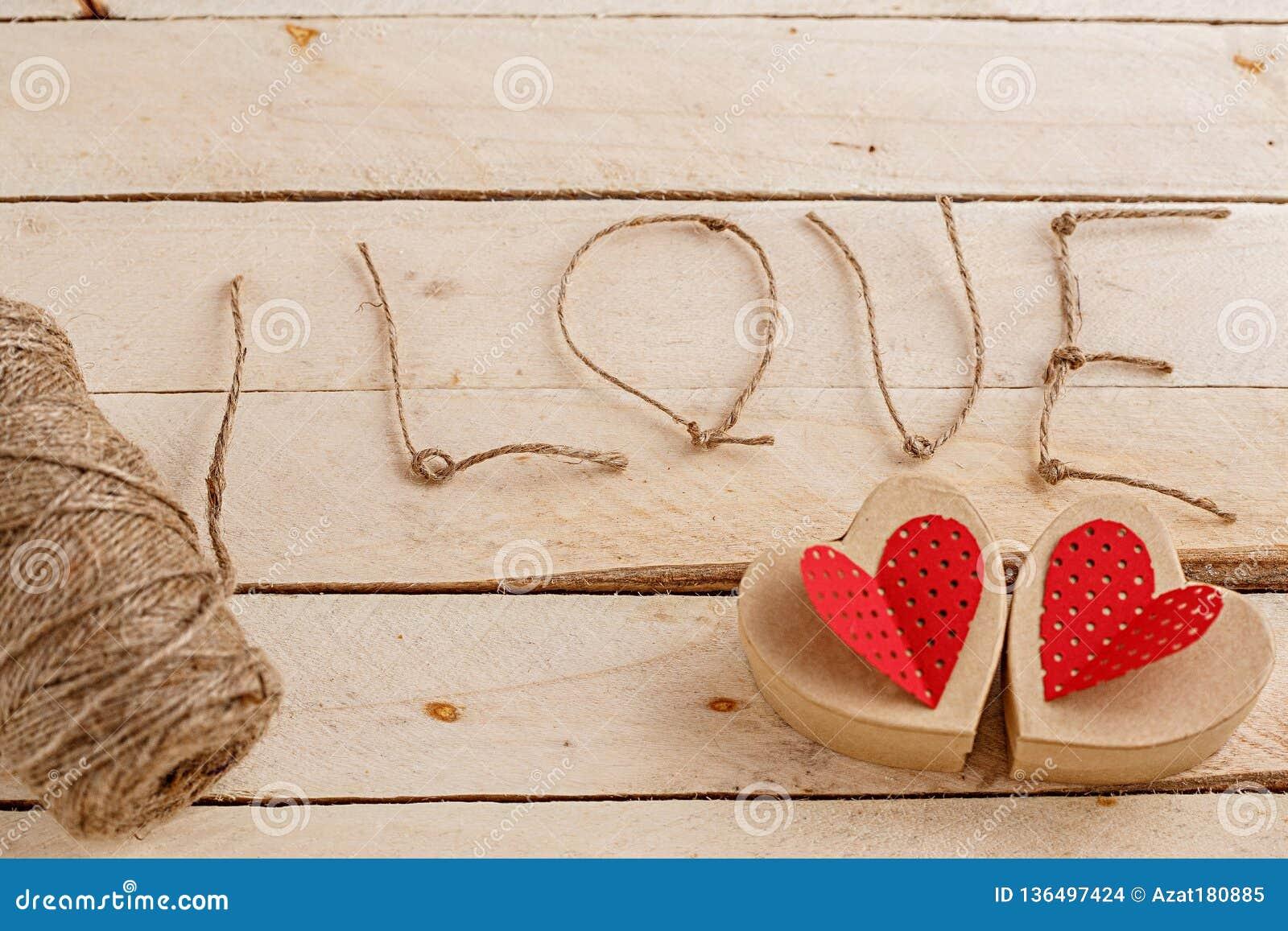 Begrepp för kärlekshistorier och för valentin dag Raden, inskrifterna från den och handgjorda papphjärtor på ett naturligt