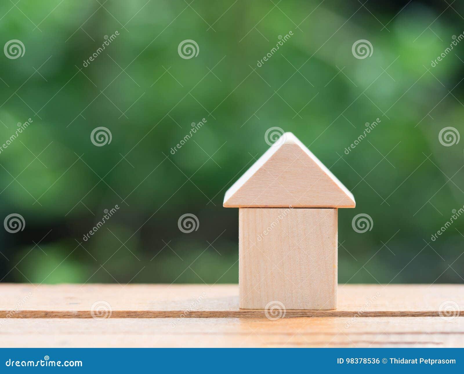 Begrepp för lånfastighethem Trähusminiatyr på trägolv med suddighetsgräsplanbakgrund