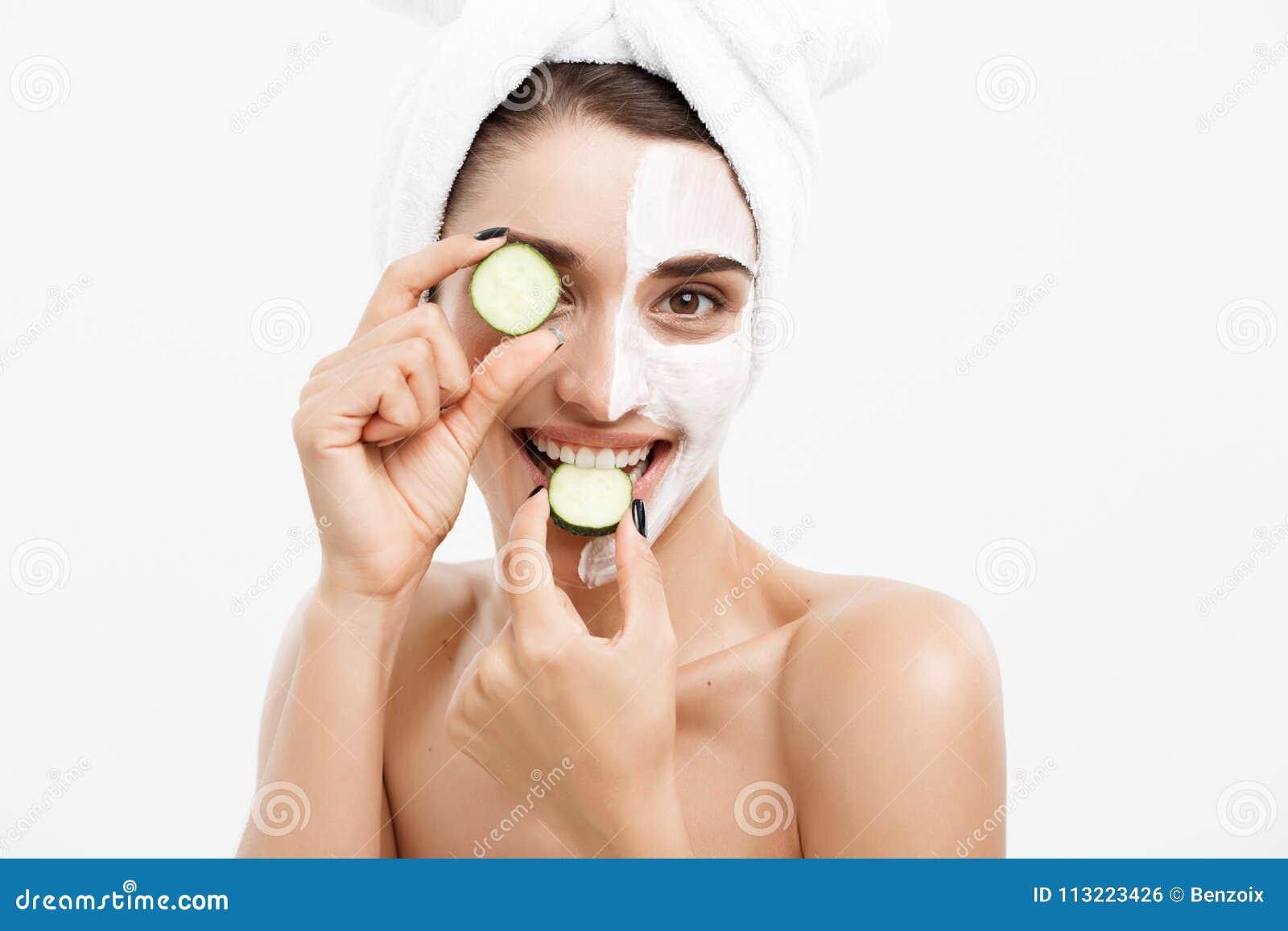 Begrepp för omsorg för skönhetungdomhud - applicerar den härliga Caucasian kvinnan för ståenden den nya gurkan för kräm och för i