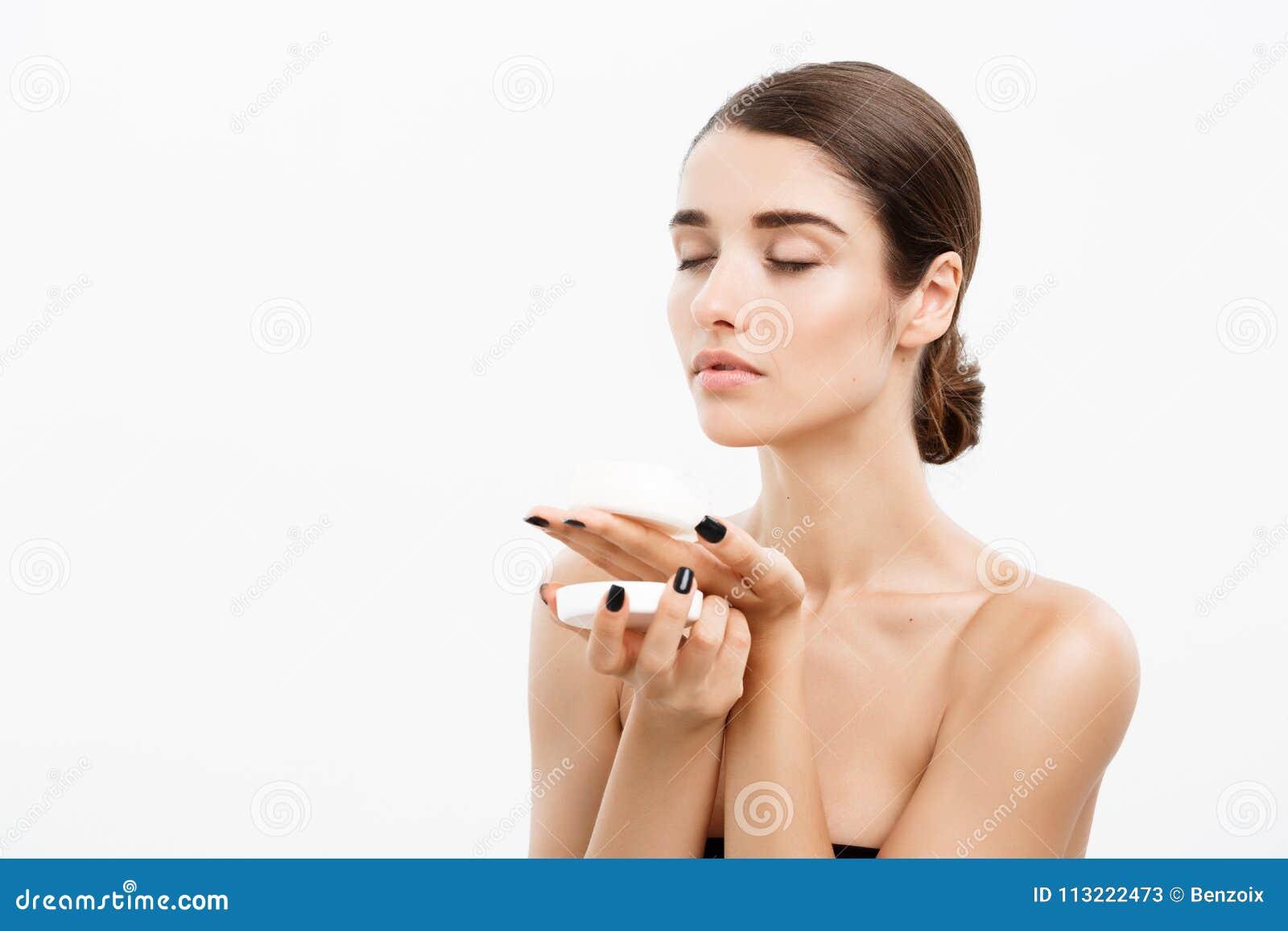 Begrepp för omsorg för skönhetungdomhud - härlig Caucasian kvinnaframsidastående som ler och rymmer den kräm- kruset för kropp oc