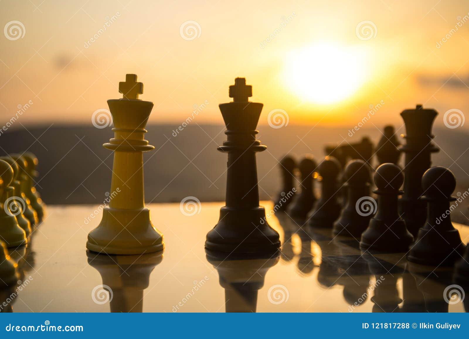 Begrepp för schackbrädelek av affärsidéer och konkurrens- och strategiidéer Schackdiagram på en utomhus- solnedgångbackgr för sch