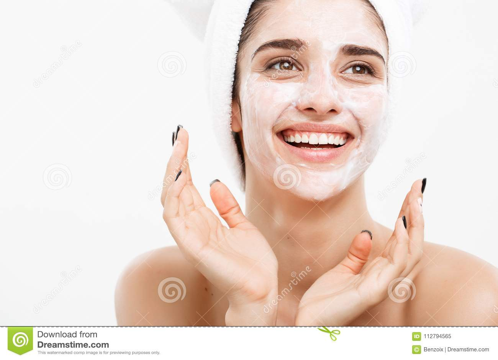 Begrepp för skönhethudomsorg - härlig caucasian kvinnaframsidastående som applicerar den kräm- maskeringen på hennes ansikts- hud