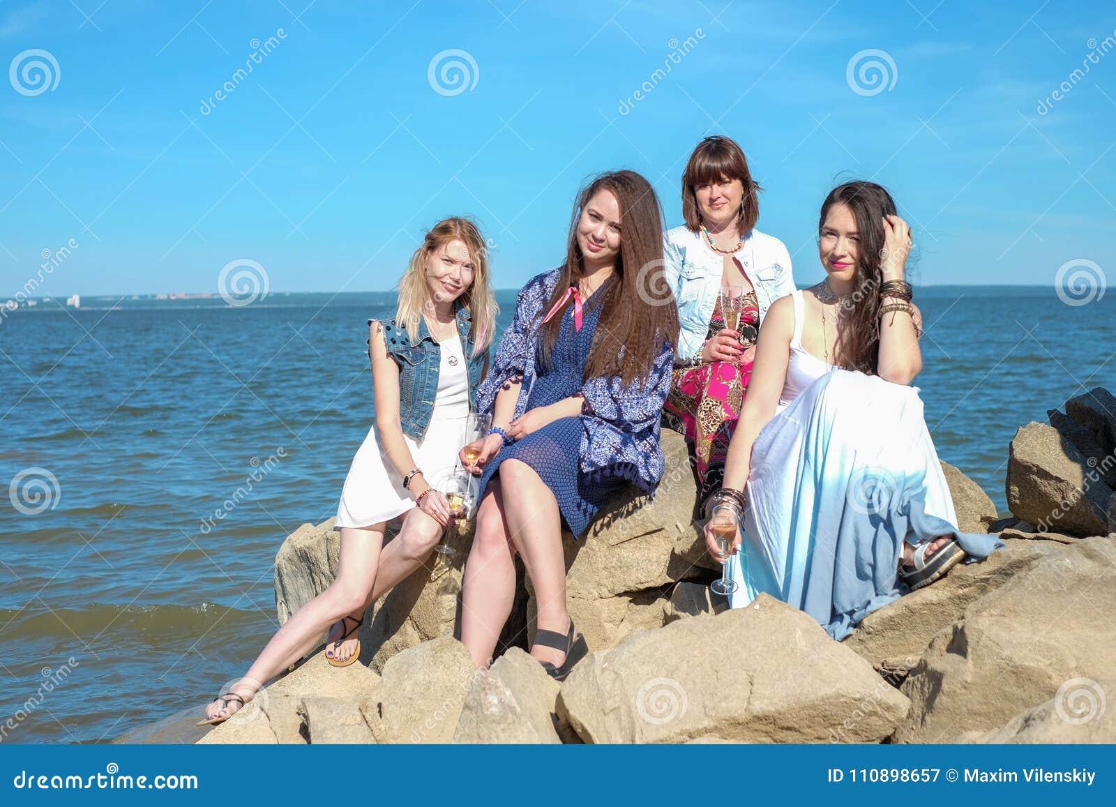 Begrepp för sommarferier - gruppen av att le unga kvinnor vilar på kusten