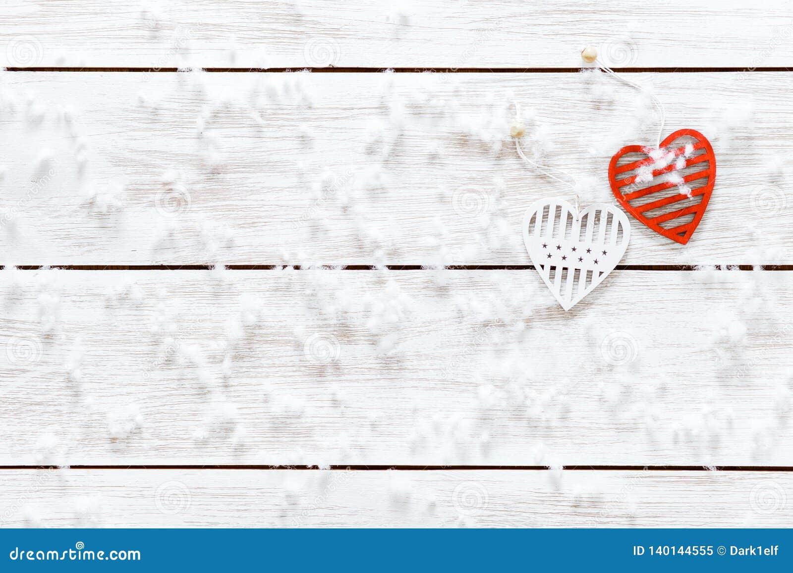 Begrepp för valentindagkort, snöflingor två vita röda hjärtor på den ljusa trätabellen som täckas med snö, romantisk feriebakgrun