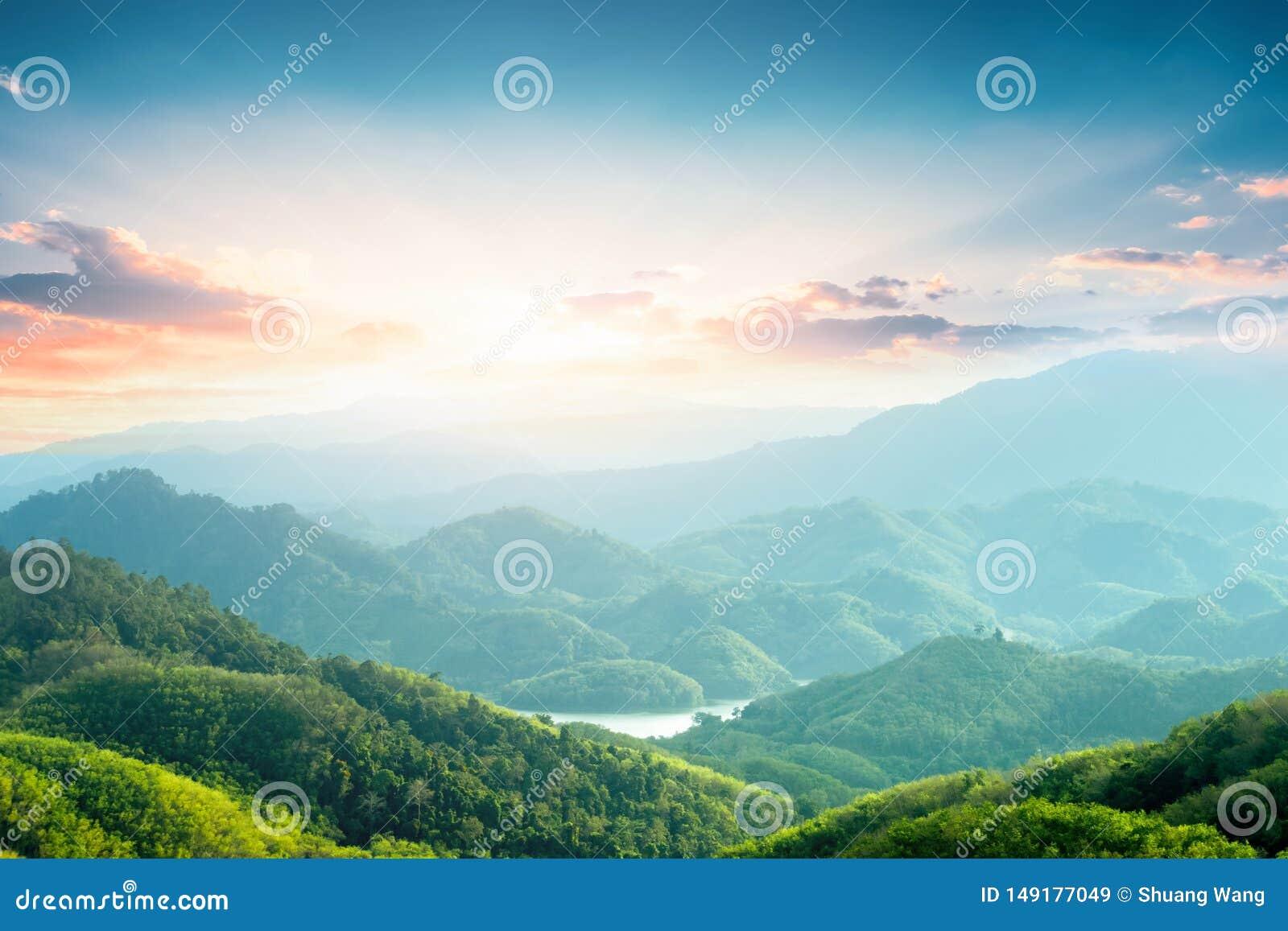 Begrepp f?r dag f?r v?rldsmilj?: Gr?na berg och h?rliga himmelmoln under den bl?a himlen