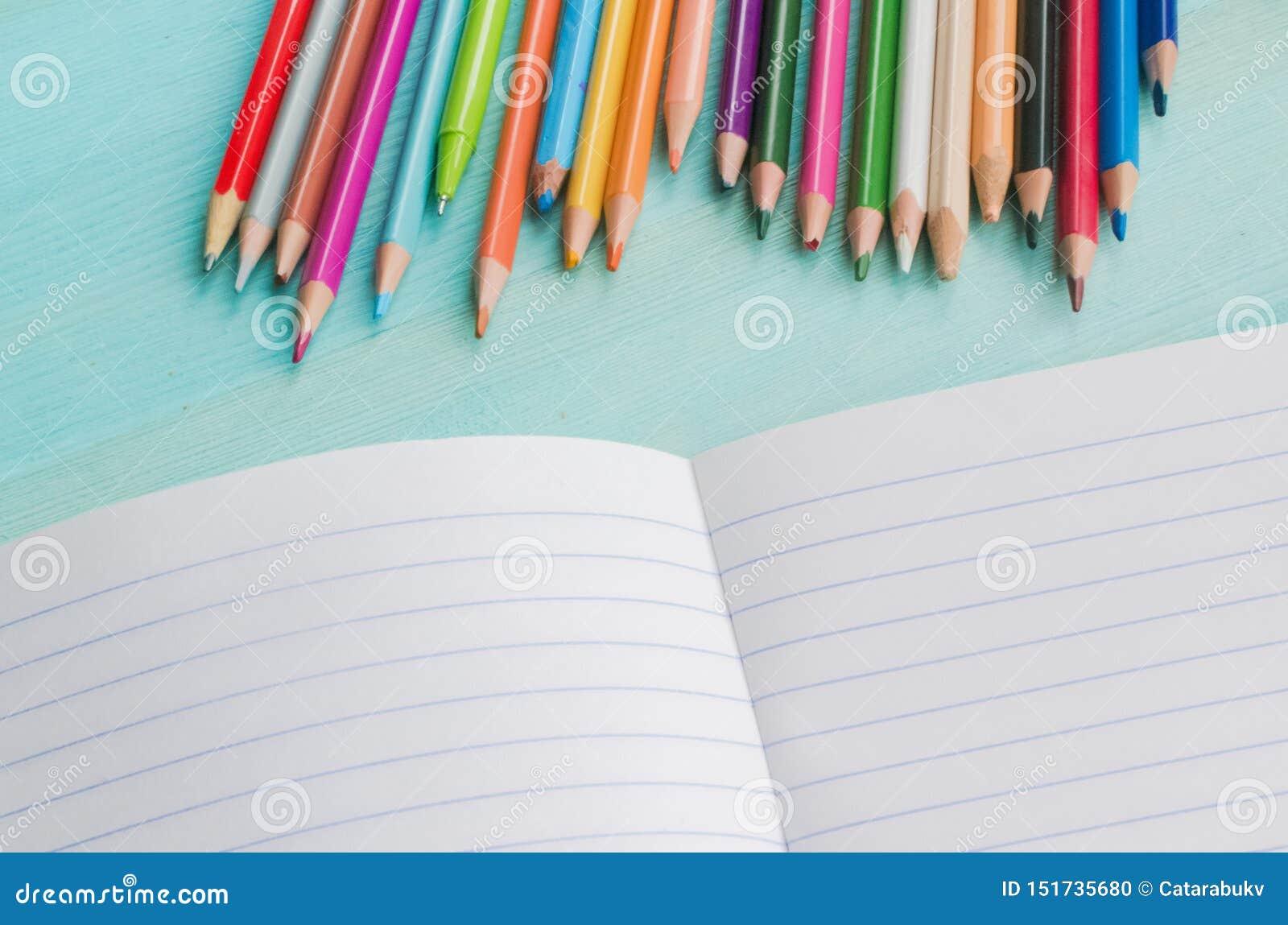 Begrepp tillbaka till skolan Skolatillbehör, kulöra blyertspennor, penna med den tomma anteckningsboken på blå träbakgrund