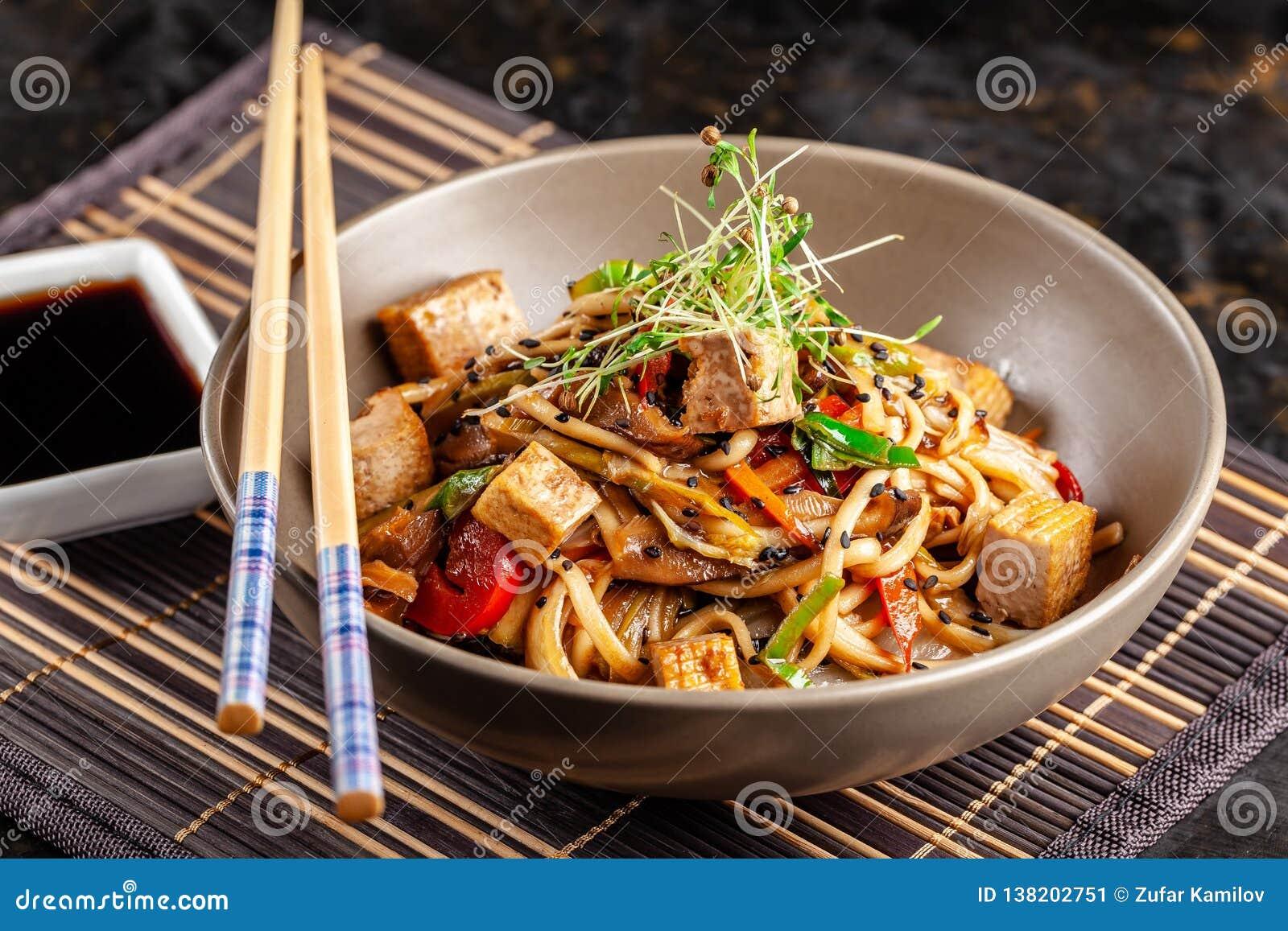 Begreppet av japansk kokkonst Kinesiska nudlar med höna, grillade grönsaker och tofuen i unagisås Tjänande som asiatisk disk