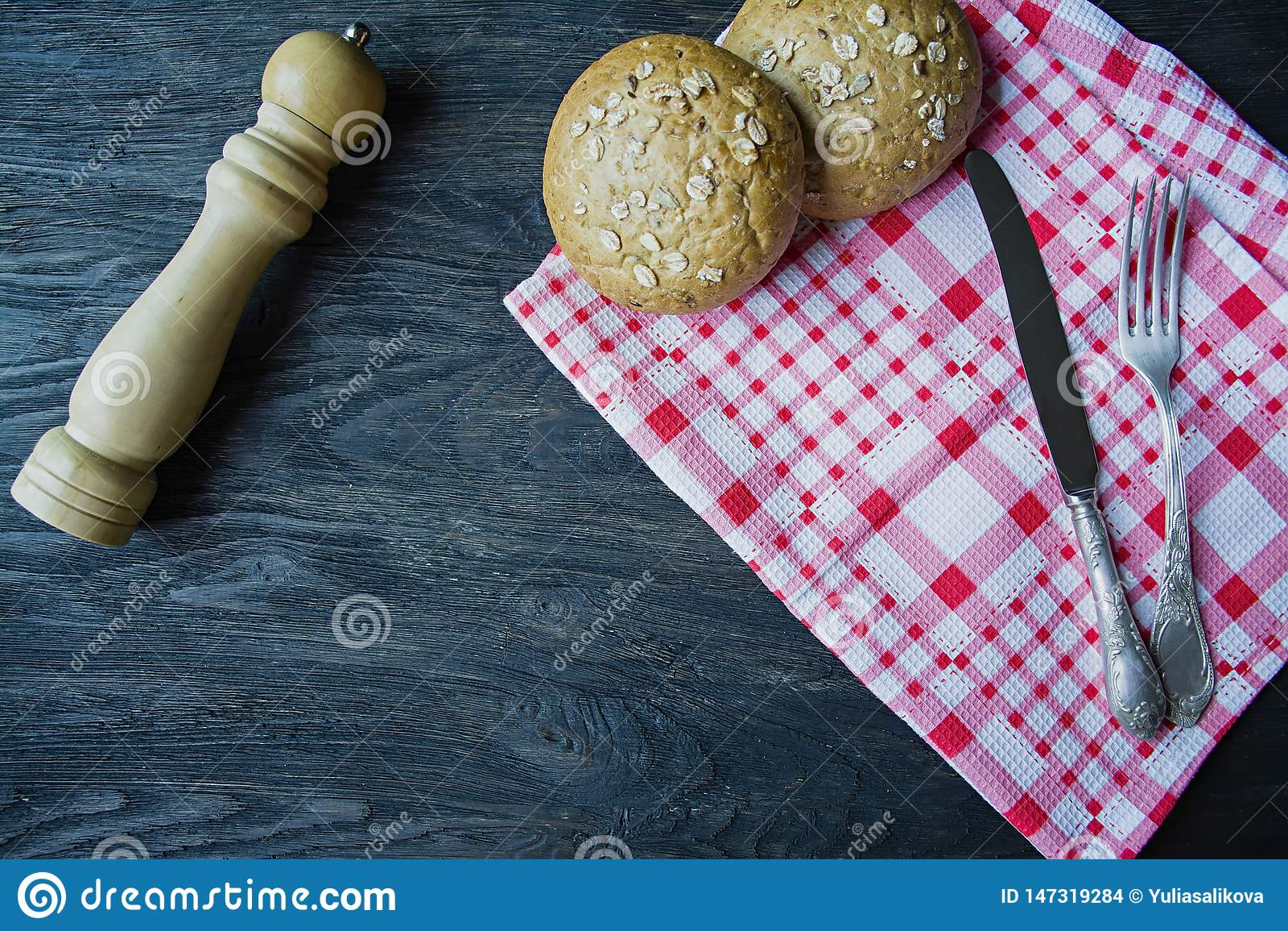 Begreppet av matlagning Gaffel matkniv, rutig servett, bullar med solrosfr?, tr?pepparshaker bestick