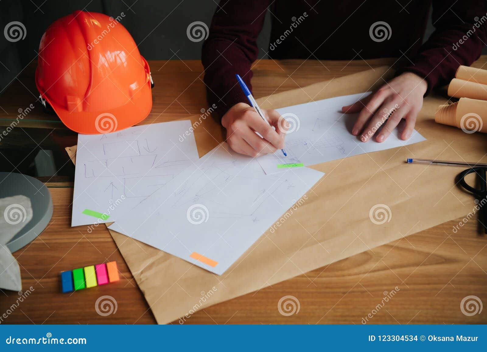 Begreppsarkitekter, iscensätter den hållande pennan som pekar utrustningarkitekter på skrivbordet med en ritning i kontoret