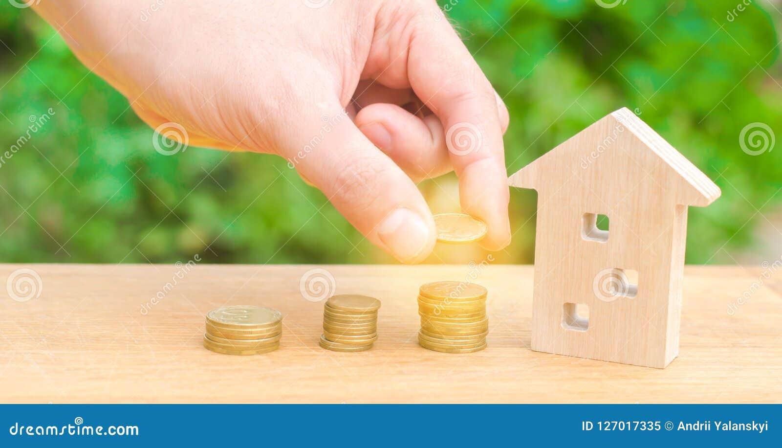 Begreppsinvestering i fastighet Sparande pengar som köper ett nytt hem Trähus och buntar av mynt från litet till stort Köpande r